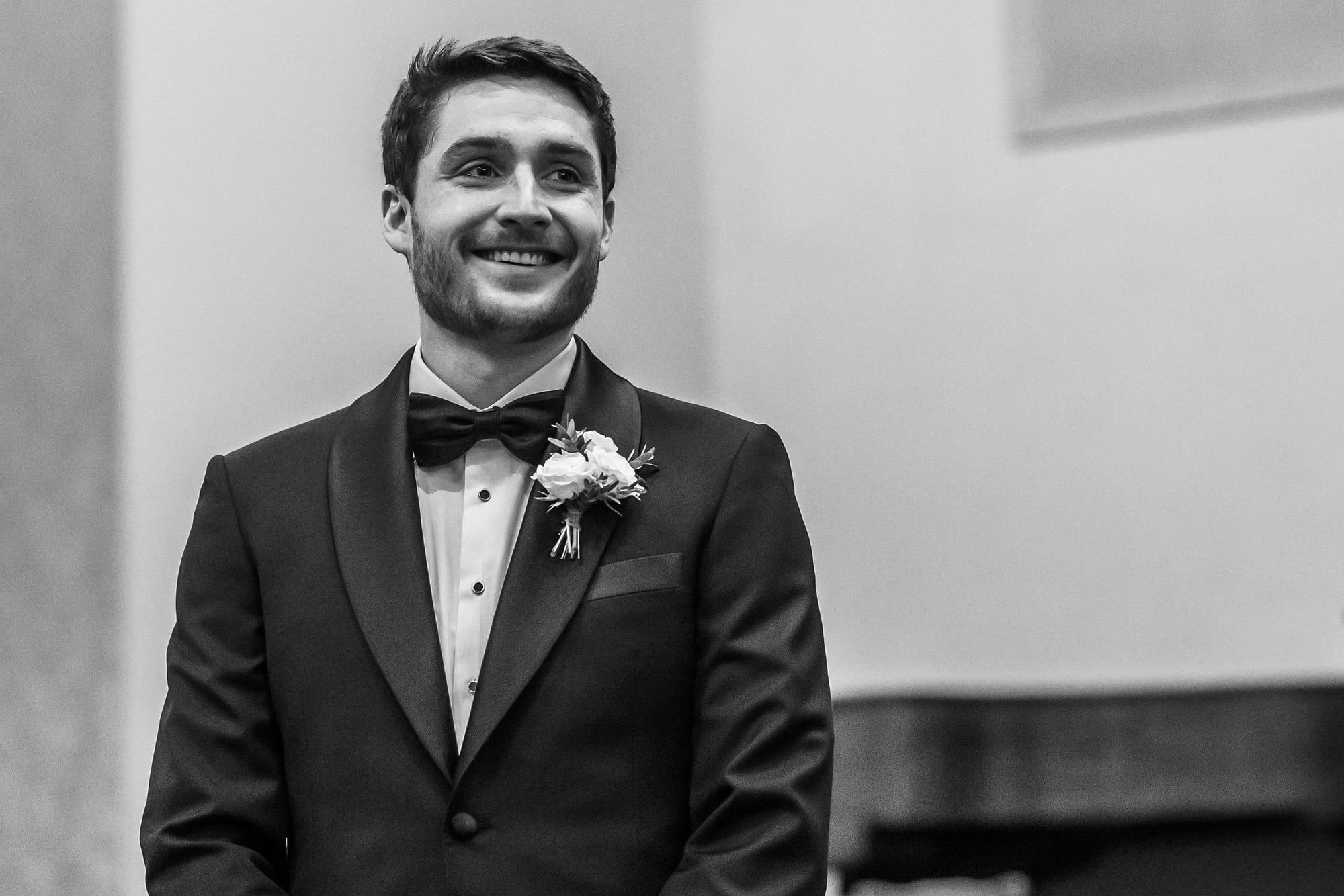Groom looks on during Blessed Sacrament Denver wedding.