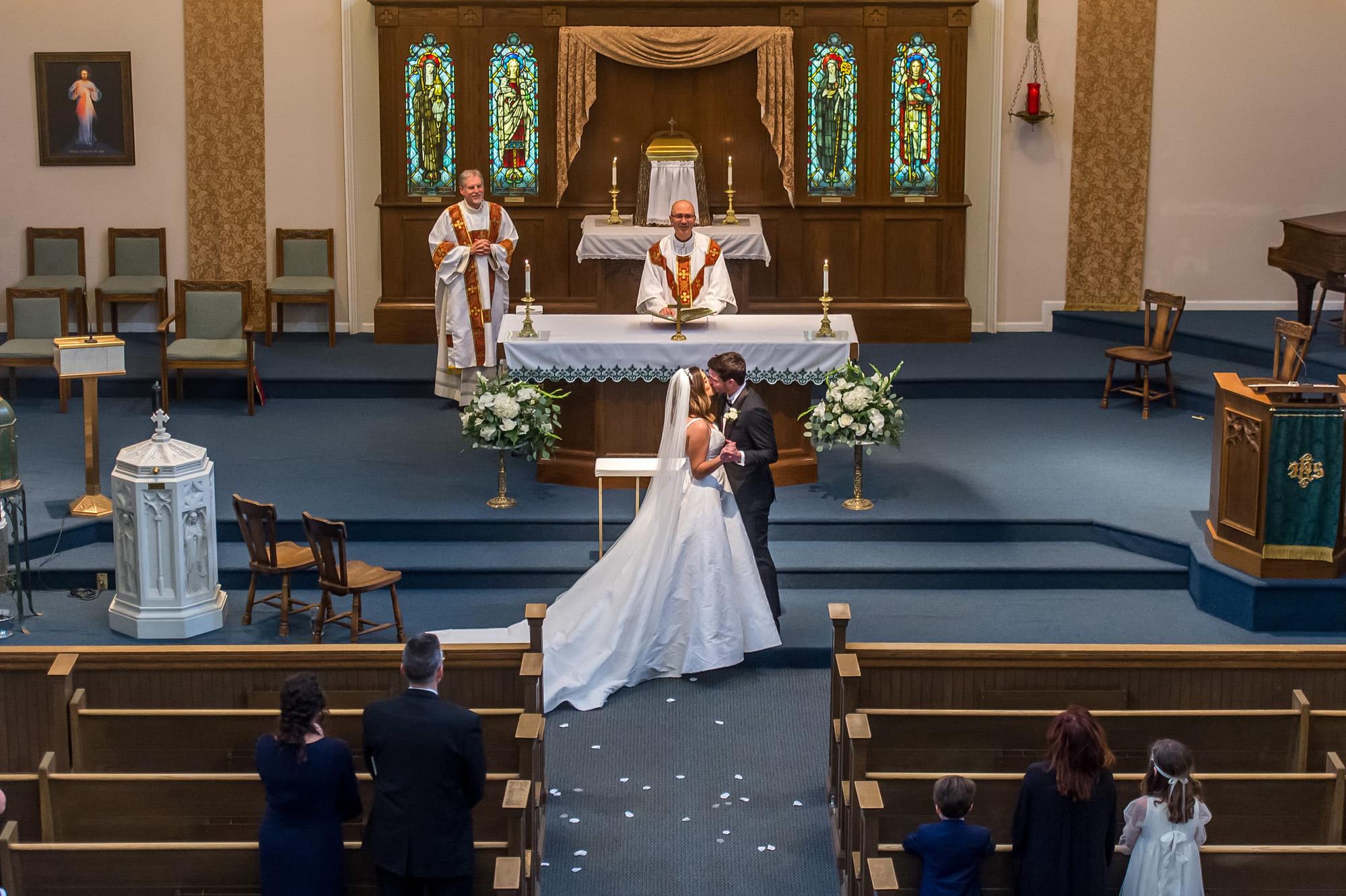 Bride and Groom kiss during a Blessed Sacrament Denver wedding ceremony.