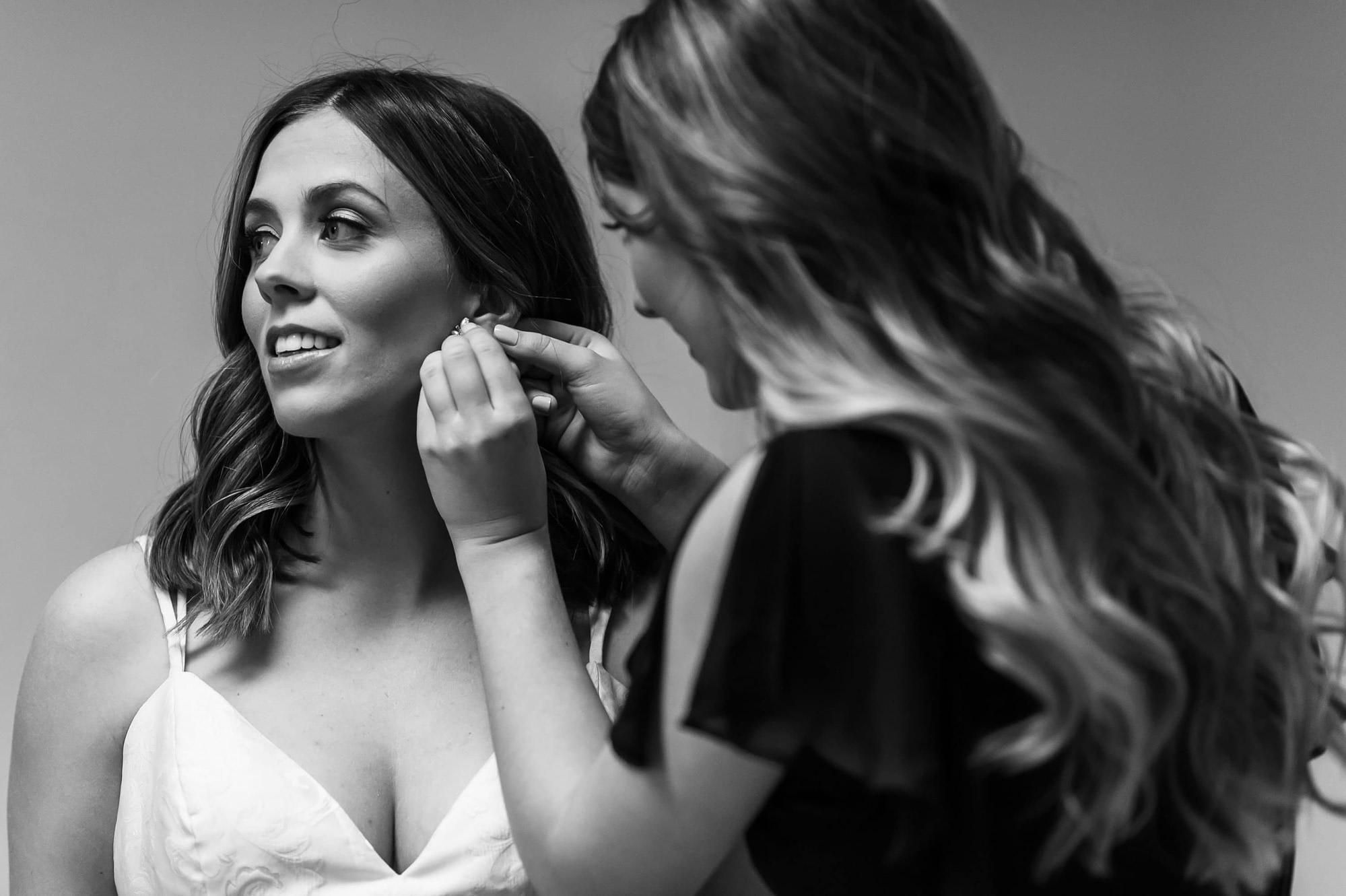 Bride gets earrings during a Blessed Sacrament Denver wedding.